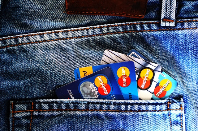 a view of a mans back pocket with several credit cards exposed